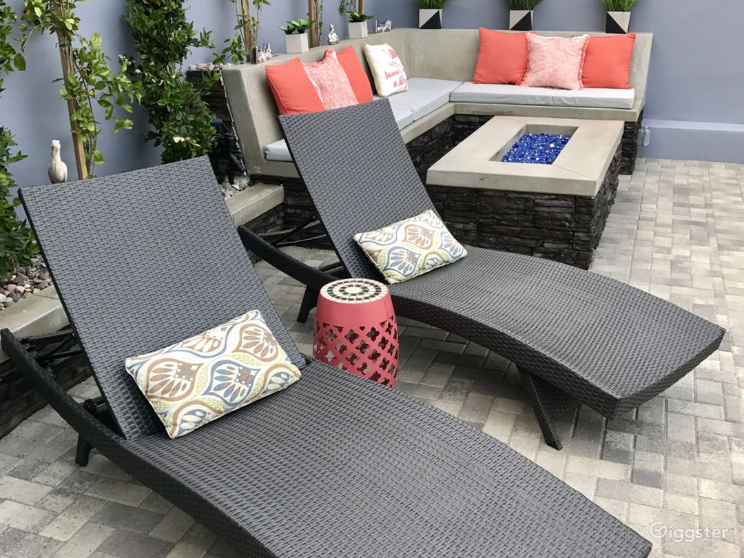 Lounge chairs by pool and fire-pit.