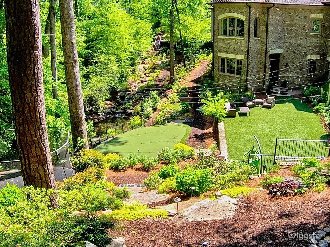 View from the full furnished guest cabin onto the turf, putting green and waterfall, stream, boulders and walking trails.