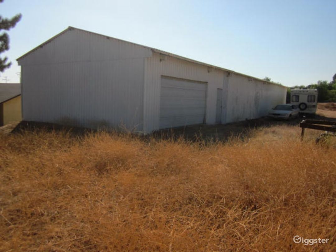 Warehouse rear left with rear overhead door & rear entrance door. Note that all dry vegetation was cleared
