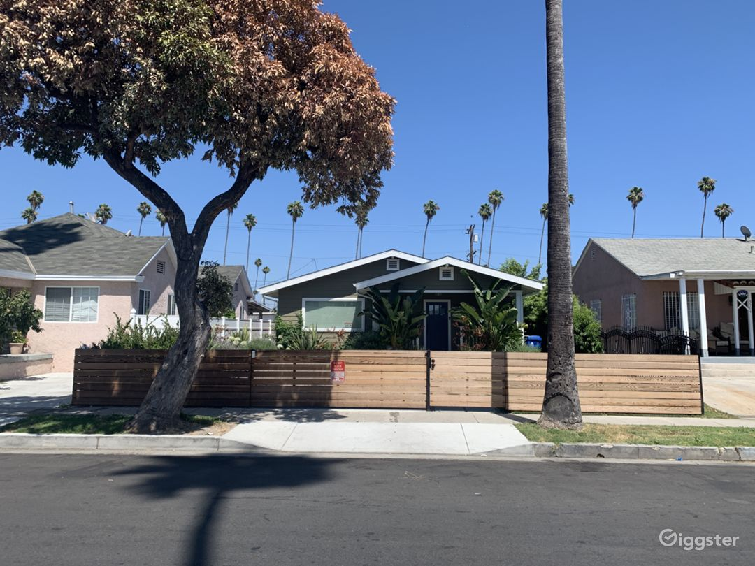Re-imagined modern craftsman bungalow with grass, native landscaping and a peach tree on a quintessential LA palm-lined street