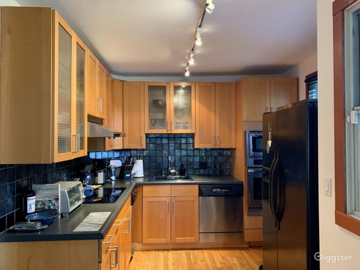 Modern kitchen with stylish black tile and black and silver appliances. Electric stovetop.