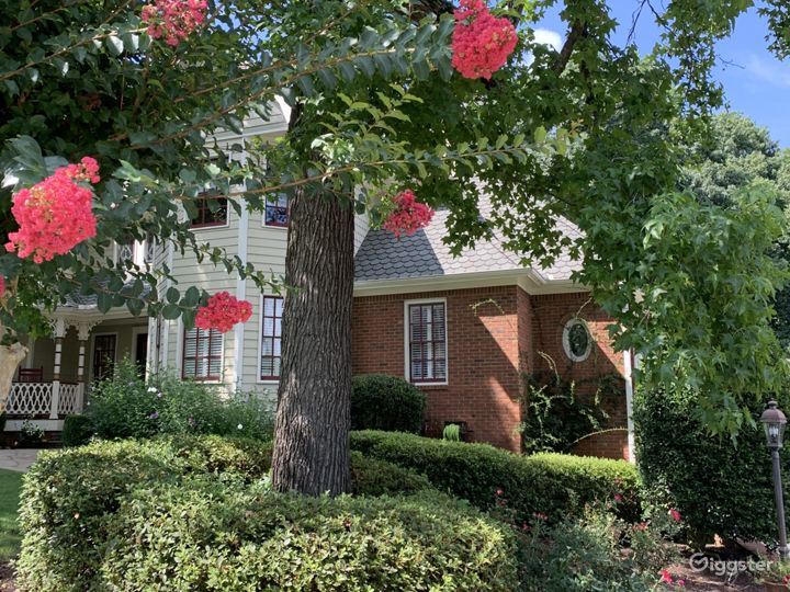 View of front house with unique oval window and gorgeous blooming flowers