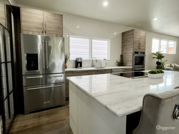 Well lit open kitchen with a huge center island. White subway tile walls floor to ceiling.