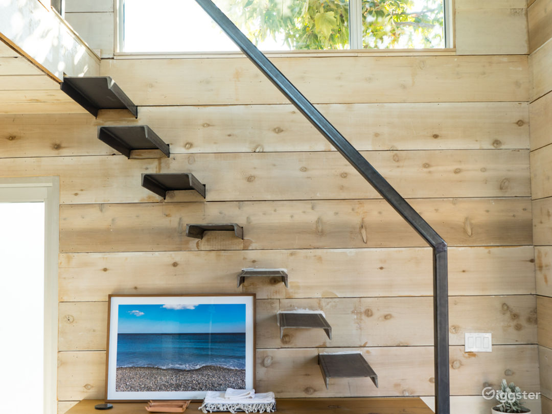 View of the raw cedar desk beneath the floating steel stairs leading up to the loft