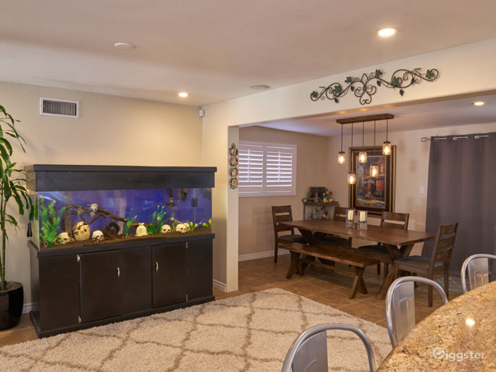 180 gallon aquarium with exotic freshwater fish. Live edge dining table and near dining area is a full-size stand up arcade machine and popcorn machine.