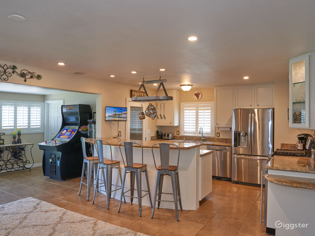 Large open kitchen with under-lighting, newly painted white cabinets and tons of counter space. Wine fridge, tv in kitchen bar, stainless appliances.  In adjacent dining area, working popcorn machine and arcade.